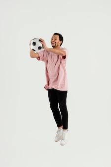 Jonge knappe man met voetbal bal springen Premium Foto
