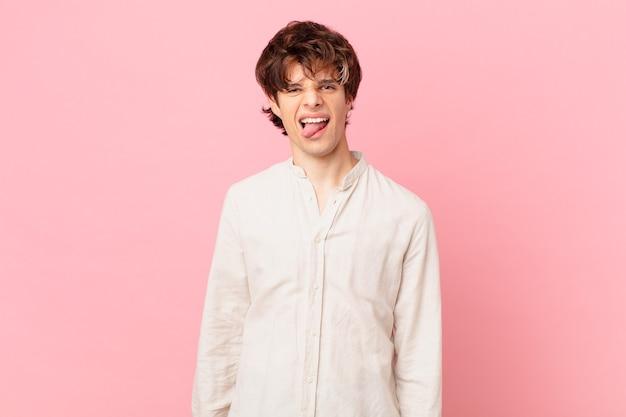 Jonge knappe man met vrolijke en opstandige houding, grappen maken en tong uitsteken