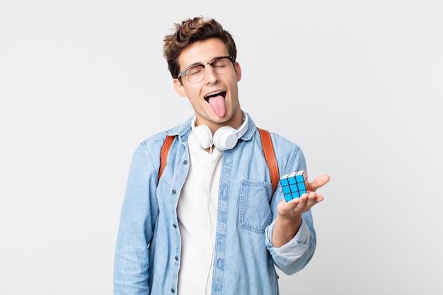 Jonge knappe man met vrolijke en rebelse houding, grappen maken en tong uitsteken. intelligentie spelconcept