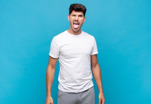 Jonge knappe man met vrolijke, zorgeloze, rebelse houding, grappen maken en tong uitsteken, plezier maken