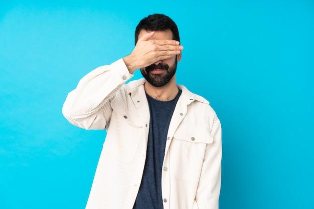Jonge knappe man met wit corduroy jasje over geïsoleerde blauwe muur die ogen behandelt door handen. wil niet iets zien