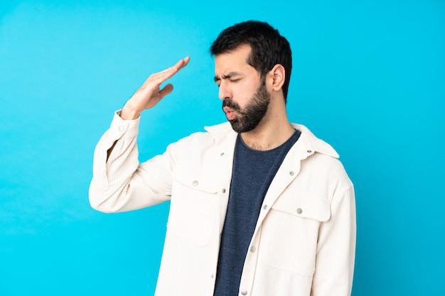 Jonge knappe man met wit corduroy jasje over geïsoleerde blauwe muur met vermoeide en zieke uitdrukking