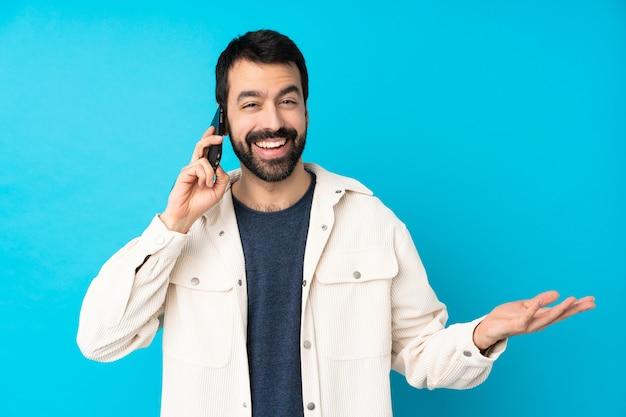 Jonge knappe man met witte corduroy jas over geïsoleerde blauwe muur houden van een gesprek met de mobiele telefoon met iemand