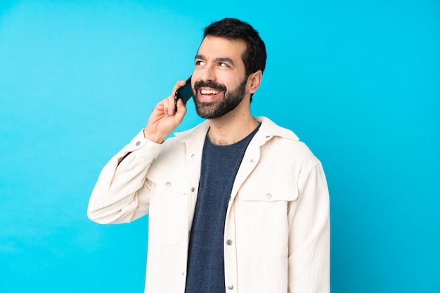 Jonge knappe man met witte corduroy jas over geïsoleerde blauwe muur houden van een gesprek met de mobiele telefoon