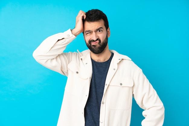 Jonge knappe man met witte corduroy jas over geïsoleerde blauwe muur met een uitdrukking van frustratie en niet begripvol