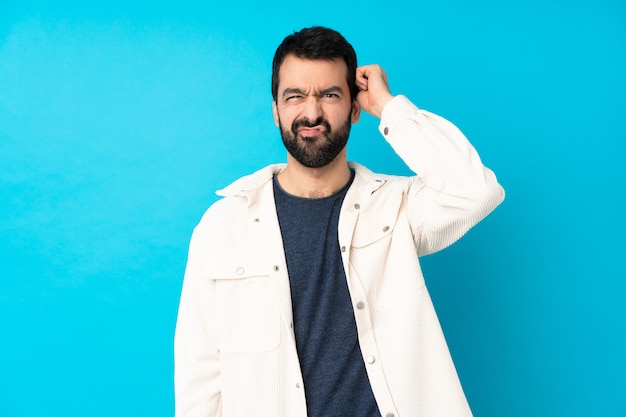 Jonge knappe man met witte corduroy jas over geïsoleerde blauwe muur met twijfels