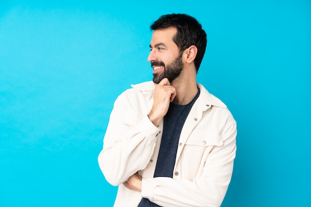 Jonge knappe man met witte corduroy jas over geïsoleerde blauwe muur op zoek naar de kant