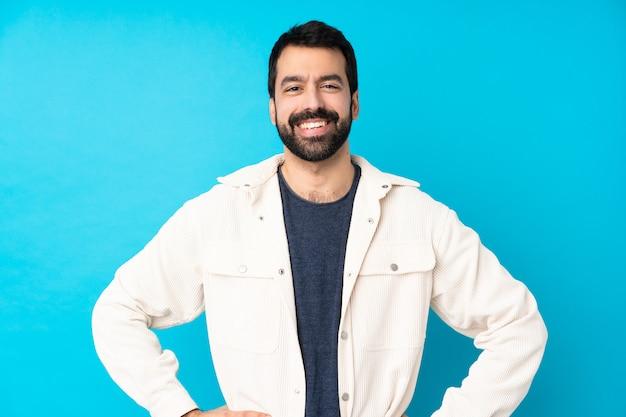 Jonge knappe man met witte corduroy jas over geïsoleerde blauwe muur poseren met armen op heup en glimlachen