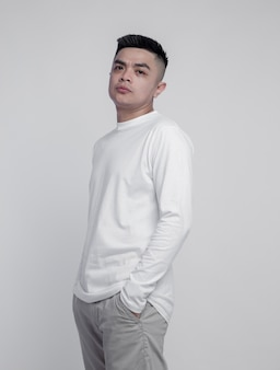 Jonge knappe man met witte t-shirt met lange mouwen geïsoleerd op een effen achtergrond