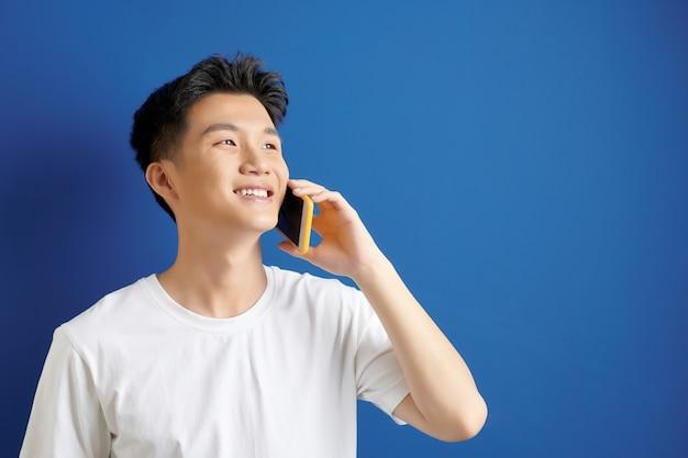 Jonge knappe man met witte t-shirt, praten over de telefoon