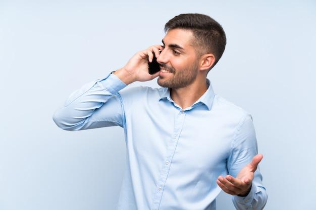Jonge knappe man met zijn mobiel over geïsoleerde blauwe muur