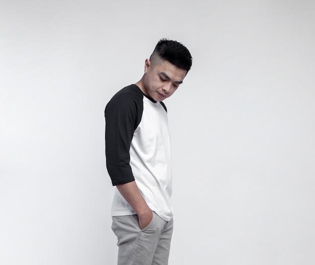 Jonge knappe man met zwart-witte raglan t-shirt geïsoleerd op de ruimte