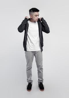 Jonge knappe man met zwarte hoodie en witte t-shirt geïsoleerd op de achtergrond