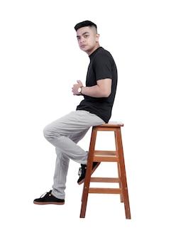 Jonge knappe man met zwarte t-shirt korte mouw zat in een stoel Premium Foto