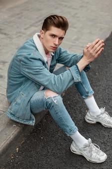 Jonge knappe man model in gescheurde vintage jeans in modieuze denim jasje in mode witte sneakers zit op tegel in de buurt van weg in de stad buiten. trendy aardige vent in stijlvolle kleding rust op straat.