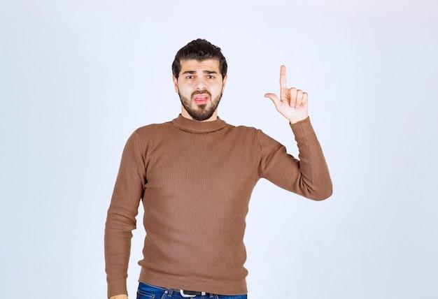 Jonge knappe man model staan en naar boven wijst.