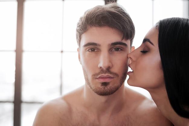 Jonge knappe man. mooie vrouw kust hem. window is achter hen. ze zijn naakt in de kamer.