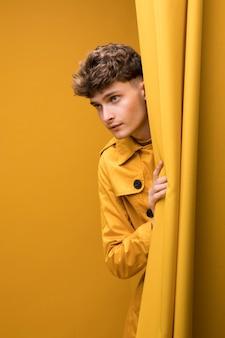 Jonge knappe man naast een gordijn in een gele scène