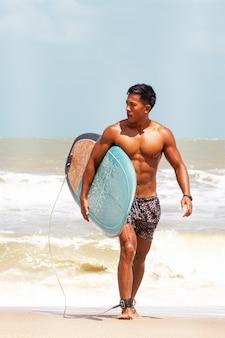 Jonge knappe man nat over het hele lichaam, met surfplank in de hand lopen op het strand