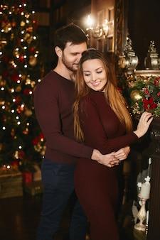 Jonge knappe man omhelst jonge vrouw in gebreide jurk in het interieur versierd voor kerstmis