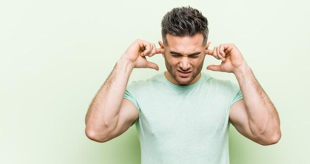 Jonge knappe man ongreen die oren bedekt met handen.