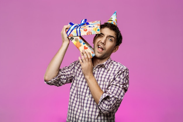 Jonge knappe man ontsnappen uit verjaardag doos over paarse muur.