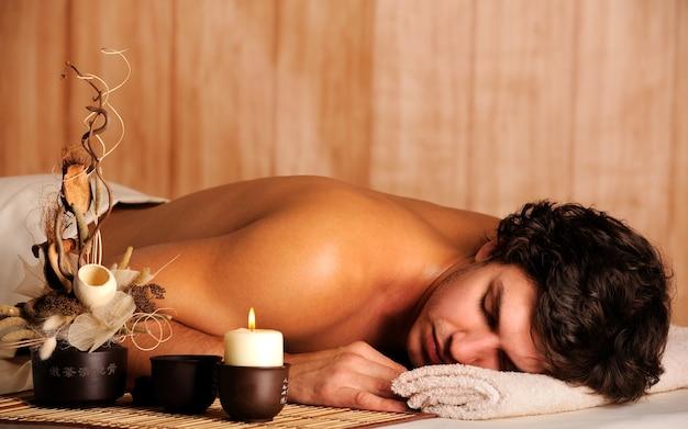 Jonge knappe man ontspannen in spa salon - hoge hoekmening