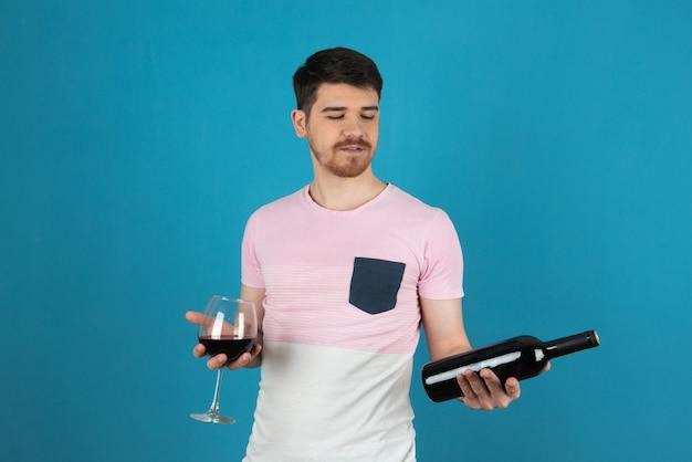Jonge knappe man op blauw terwijl hij een glas wijn en een wijnfles vasthoudt.