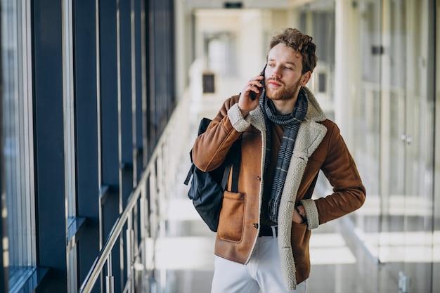 Jonge knappe man op de luchthaven praten aan de telefoon