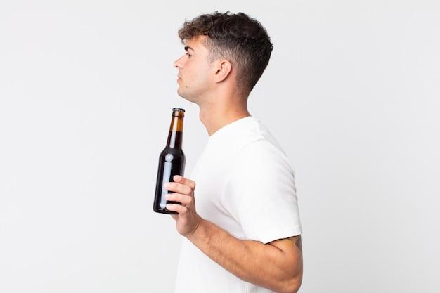 Jonge knappe man op profielweergave denken, fantaseren of dagdromen en een bierflesje vasthouden