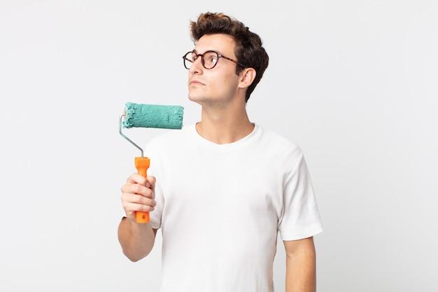 Jonge knappe man op profielweergave denken, fantaseren of dagdromen en een verfroller vasthouden