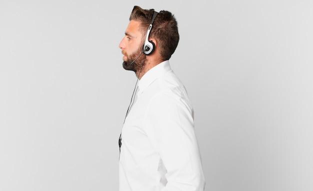 Jonge knappe man op profielweergave denken, fantaseren of dagdromen. telemarketing concept