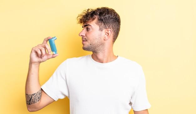 Jonge knappe man op profielweergave denken, verbeelden of dagdromen. astma concept