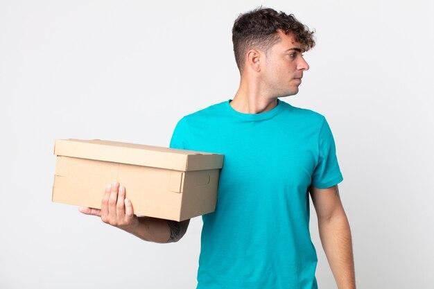Jonge knappe man op profielweergave denken, verbeelden of dagdromen en een kartonnen doos vasthouden