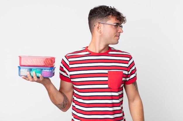 Jonge knappe man op profielweergave denken, verbeelden of dagdromen en een lunchbox vasthouden