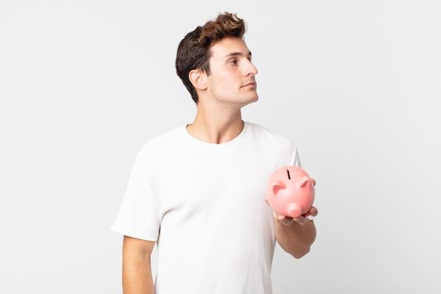 Jonge knappe man op profielweergave denken, verbeelden of dagdromen en een spaarvarken vasthouden