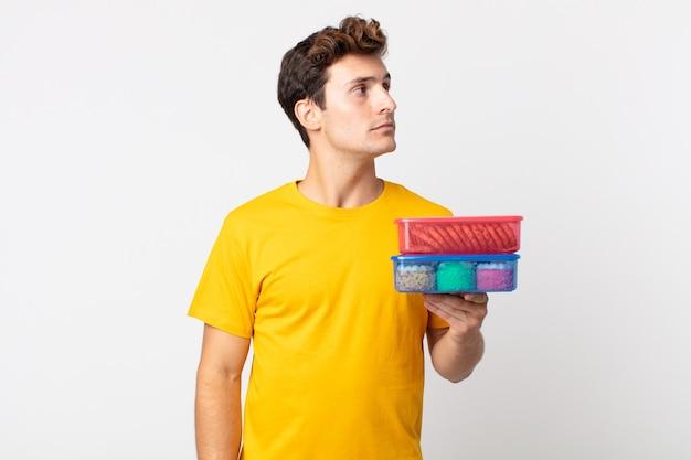 Jonge knappe man op profielweergave denken, verbeelden of dagdromen en lunchboxen vasthouden