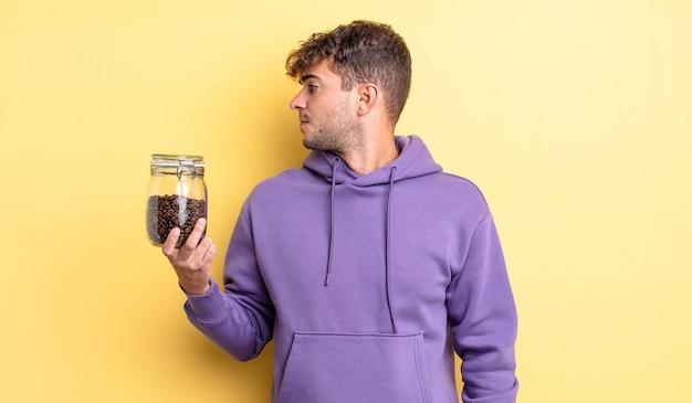 Jonge knappe man op profielweergave denken, verbeelden of dagdromen. koffiebonen concept