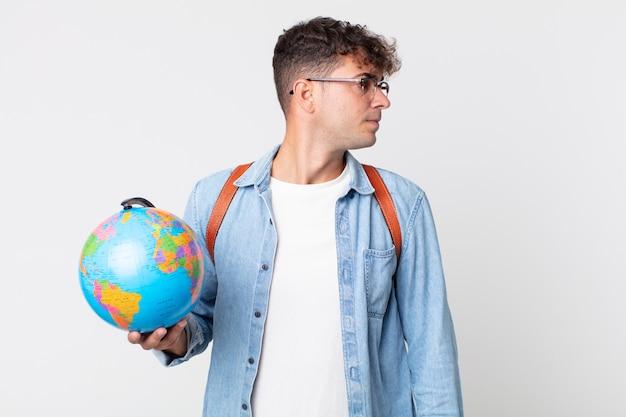 Jonge knappe man op profielweergave denken, verbeelden of dagdromen. student met een wereldbolkaart