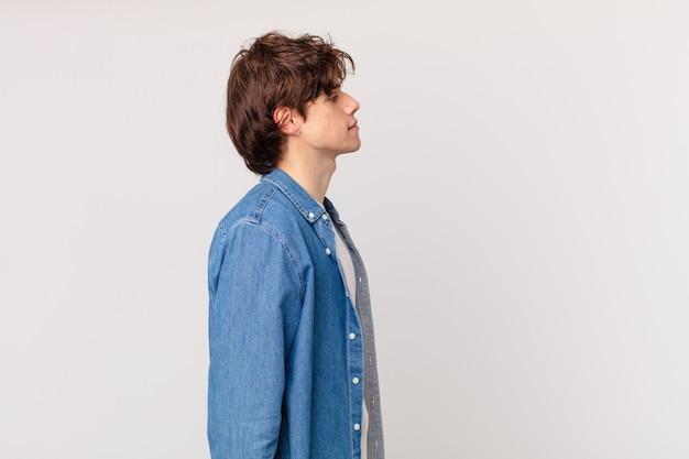 Jonge knappe man op profielweergave denken, verbeelden of dagdromen Premium Foto