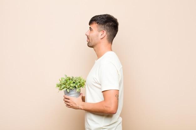 Jonge knappe man op profielweergave die ruimte vooruit wil kopiëren, denkend, verbeeldend of dagdroomend met een plant