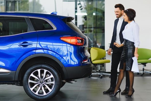 Jonge knappe man op showroom staande in de buurt van auto