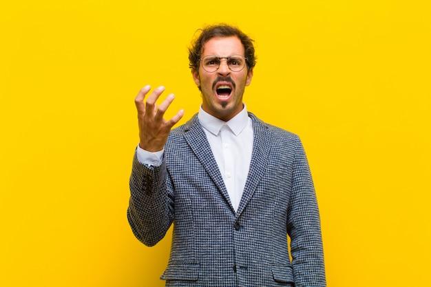 Jonge knappe man op zoek boos, geërgerd en gefrustreerd schreeuwen wtf of wat is er mis met je tegen oranje muur