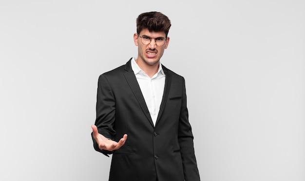 Jonge knappe man op zoek boos, geïrriteerd en gefrustreerd schreeuwen wtf of wat is er mis met je