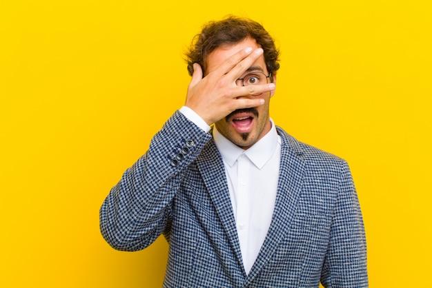 Jonge knappe man op zoek geschokt, bang of doodsbang, die gezicht bedekt met hand en gluren tussen vingers tegen sinaasappel