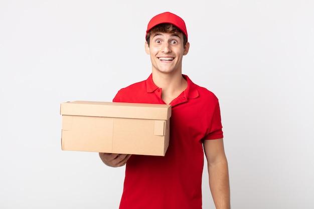 Jonge knappe man op zoek naar blij en aangenaam verrast levering pakket dienstverleningsconcept.