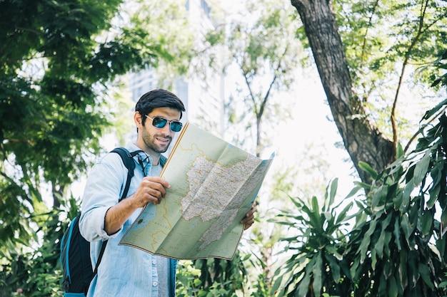 Jonge knappe man op zoek naar papieren kaart en het gebruik van zonnebril in openbaar park met een blij gezicht staan en glimlachen
