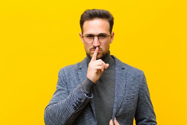 Jonge knappe man op zoek serieus en kruis met vinger tegen lippen gedrukt die stilte of stilte eisen, en een geheime oranje muur bewaren
