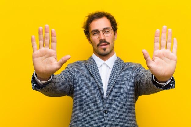 Jonge knappe man op zoek serieus, ongelukkig, boos en ontevreden verbieden toegang of zeggen stop met beide open palmen tegen oranje muur