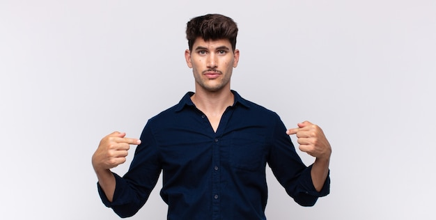 Jonge knappe man op zoek trots, positief en casual wijzend naar de borst met beide handen
